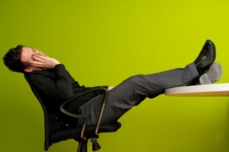 Giovane uomo in camicia nera, dormendo in sedia con gambe sul tavolo