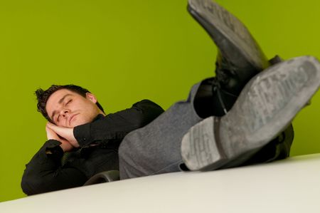 workless: Young man in black shirt sleeping in chair with legs on table