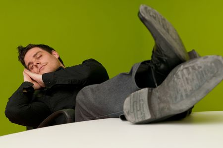 Young man in black shirt sleeping in chair with legs on table Stock Photo - 6880875