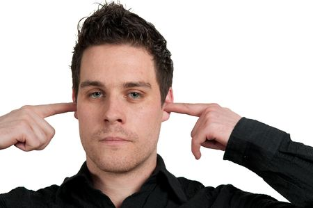 Portrait of young man with fingers in ear not listening isolated on white