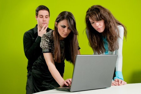 Two women being watched bytheir male colleague in the office Stock Photo