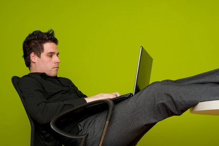 Closeup of young man working on laptop with legs on the table photo