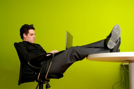 feet on desk: Closeup of young man working on laptop with legs on the table Stock Photo