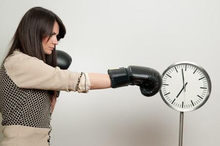 paliza: Mujer joven en guantes de boxeo, venciendo al reloj Foto de archivo