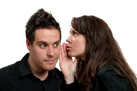 Young attractive girl whispering to a young man Standard-Bild