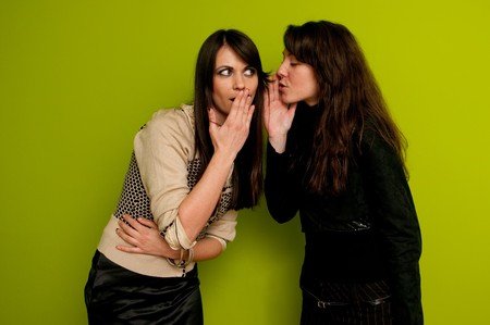 Young attractive girl whispering to her friend photo