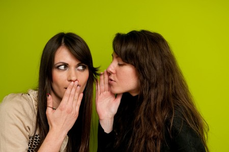 Young attractive girl whispering to her friend Standard-Bild