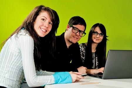 Two attractive girls and a guy working in office with green background photo
