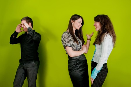 excluded: Two female colleagues gossiping and man holding his head in disbelief