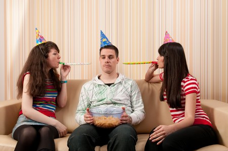 Two girls and a guy in party hats having a birthday party photo