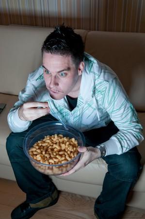 Giovane uomo mangiare snack e guardando la televisione Archivio Fotografico