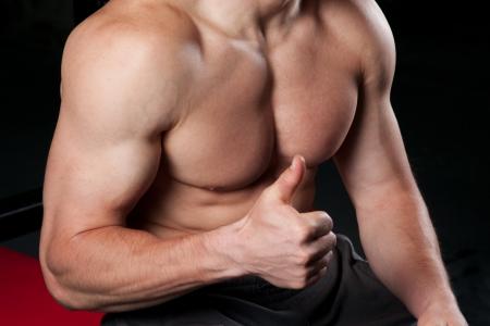 Ritaglio di un uomo muscoloso, dando un segno ok