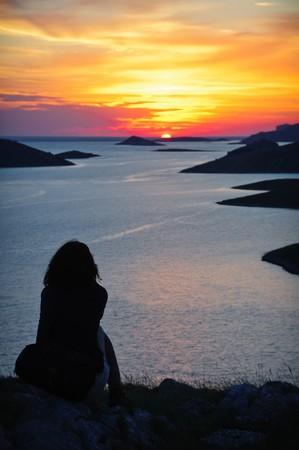 mujer mirando el horizonte: Silueta de una mujer viendo la puesta de sol de oro sobre mar