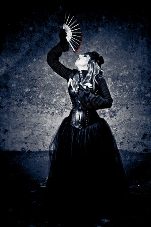 Witch in black dress drinking blood dripping from a fan photo
