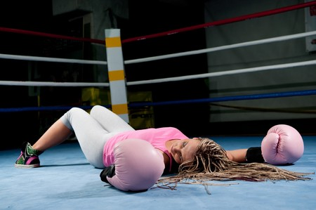 Pretty female boxer knocked out laying on the floor Stock Photo - 8080180