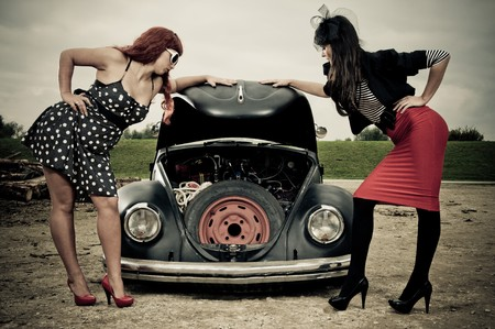Two elegant 50s style girls looking at car engine