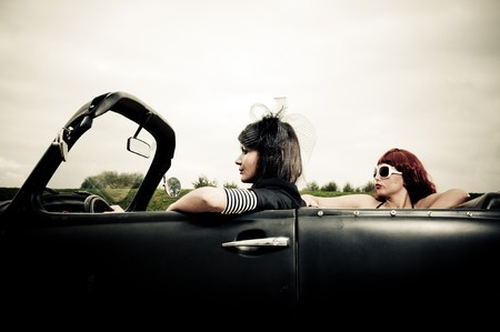 Side view of two attractive girls driving around in vintage car photo