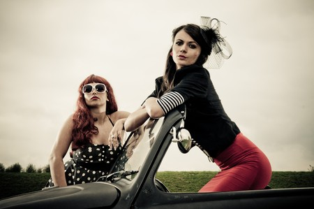 Two attractive retro 50s style dressed girls posing on car photo