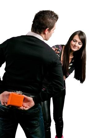 Uomo di nascondere un regalo per gril dietro la schiena, isolata on white