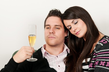 Young couple sitting, man drinking champagne and girl resting her head on his photo