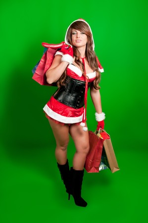 Sexy girl Santa holding a bunch of shopping bags on green background photo