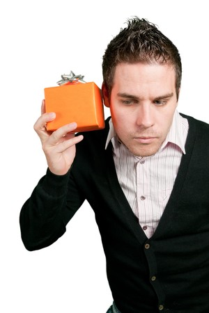 Young man curious whats inside gift box on green background
