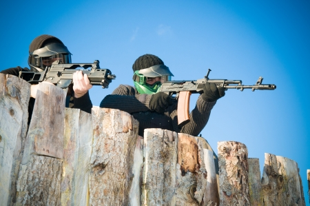 Airsoft players with protective masks shooting Standard-Bild
