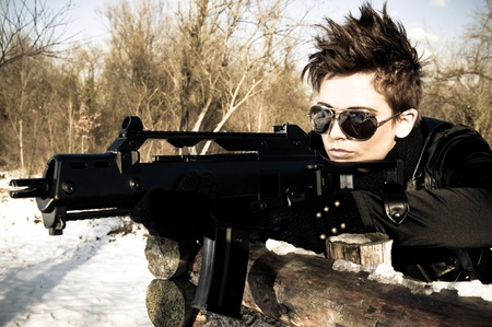 Sexy girl with sunglasses aiming a machine gun