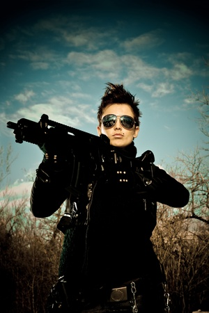 Sexy girl with sunglasses posing with a machine gun Stock Photo - 8437937