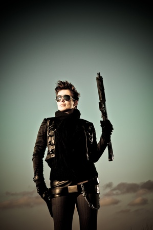 Sexy girl with sunglasses posing with a machine gun photo