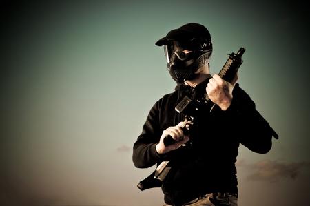 Airsoft giocatore con protezione mash detiene una mitragliatrice