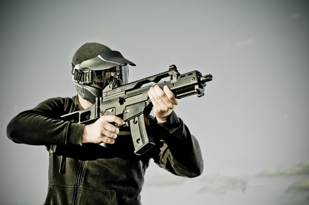 Airsoft player with protective mash holding a machine gun