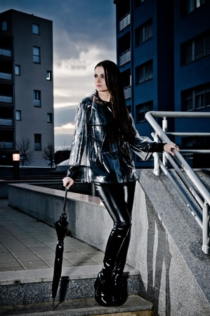 inclement weather: Tall thin sexy woman in tight leathers and a transparent raincoat standing with her umbrella on urban steps. Stock Photo
