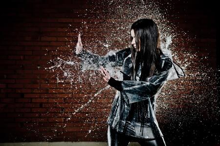 fend: Woman In Giocando pioggia con gocce d'acqua a spruzzo intorno a lei mentre cerca di allontanare fuori con le mani.