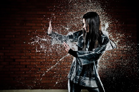 raincoat: Woman Playing In Rain with water droplets spraying all around her as she tries to ward it off with her hands.