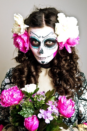 mexican folklore: A woman in Halloween costume and skull makeup holding flowers