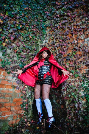 Attractive scared girl in red hood leaning on brick wall photo