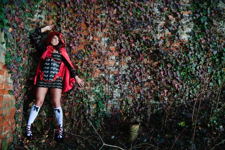 Atractive scared girl in red hood leaning on brick wall photo