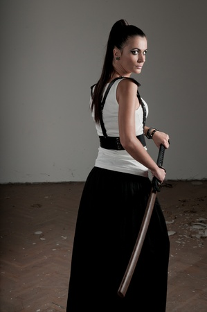 Beautiful woman holding a sheathed sword looking back photo