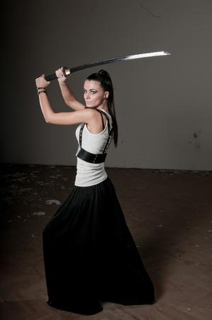 Bella donna che impugna una spada lunga in acciaio lucente cerimoniale sopra la sua testa Archivio Fotografico
