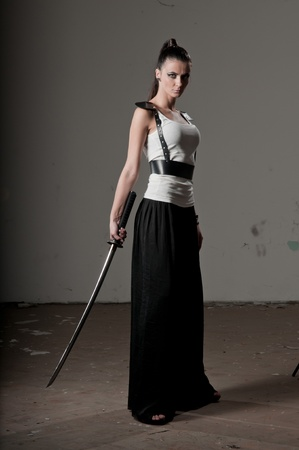 Beautiful woman holding a long steel sword Standard-Bild
