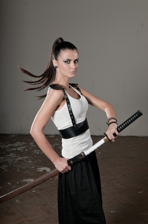 Beautiful woman unsheathing long steel sword while turning her head Stock Photo