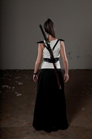 Bella donna con la schiena verso la telecamera e katana sulla schiena Archivio Fotografico