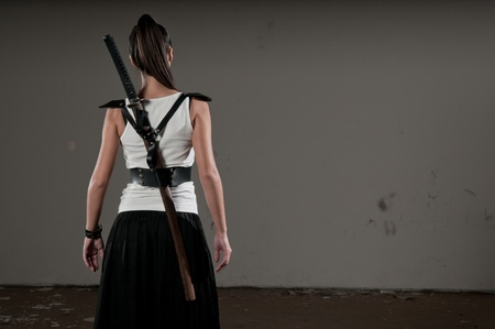 Beautiful woman with her back towards the camera and katana on her back photo