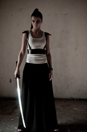 Beautiful woman holding a long shining steel ceremonial sword photo