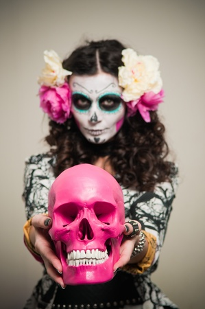 demonic: A woman in Halloween costume and skull makeup holding flowers