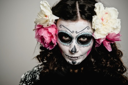 halloween skeleton: A woman in Halloween costume and skull makeup holding flowers