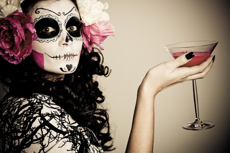 A woman in Halloween costume Holding a Glass With Red Liquid photo