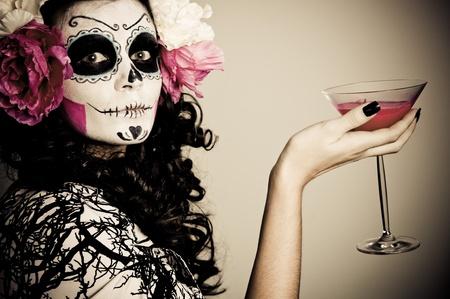 traje mexicano: Una mujer en el disfraz de Halloween sosteniendo un vaso con líquido rojo Foto de archivo