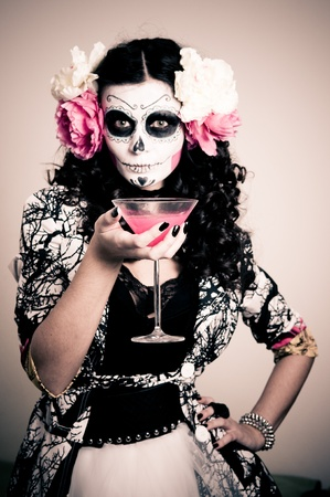 A woman in Halloween costume Holding a Glass With Red Liquid Stock Photo